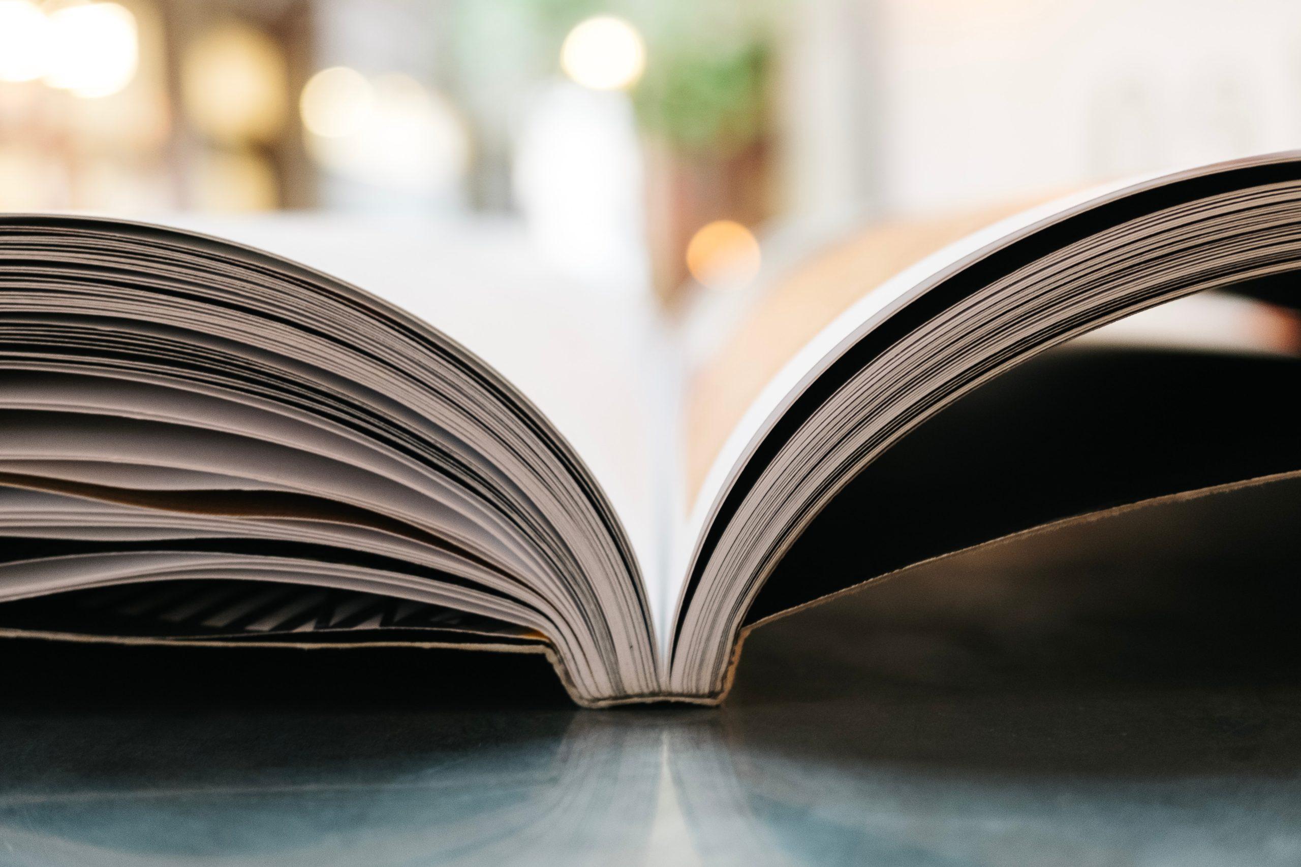 Pöydällä on avonainen kirja.