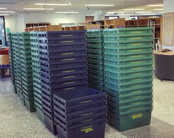 Kuvassa näkyy pinoittain muuttolaatikoita tyhjässä kirjastosalissa