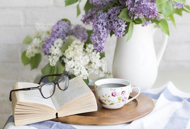 Pöydällä tarjotin, jonka päällä kirja ja kahvikuppi. Kirjan päällä silmälasit. Tarjottimen takana kukkamaljakko.
