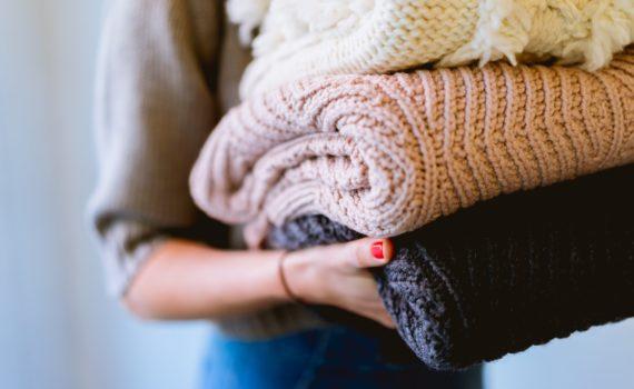 Nainen kantaa sylissään erivärisiä vilttejä.