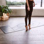Nainen seisoo jumppamaton reunalla varpaisillaan.