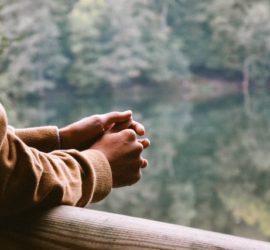 Ihminen seisoo järven rannalla ja nojaa puiseen aitaan.